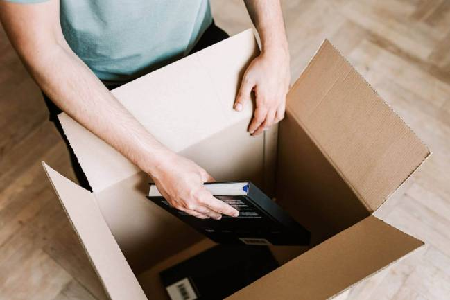 Person packing books into box.