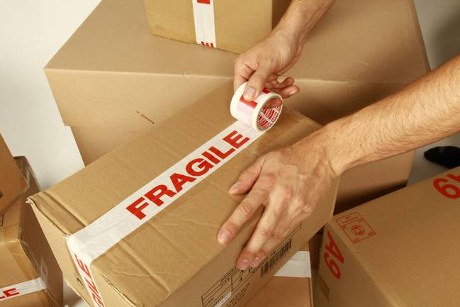"""Person putting tape marked """"fragile"""" on box."""