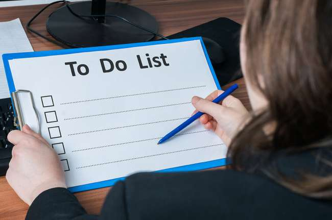 Woman writing on to do list.