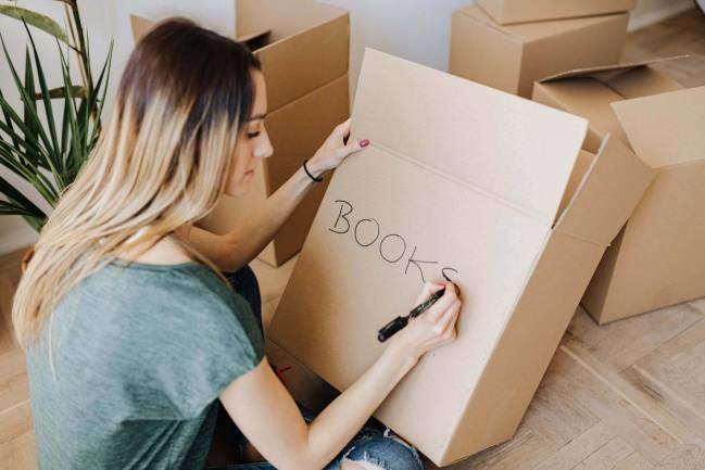 Woman writing label on box.