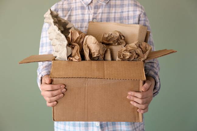 Person holding box with various papers.