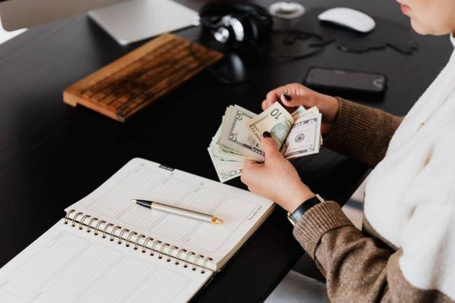 Woman at desk counting money.