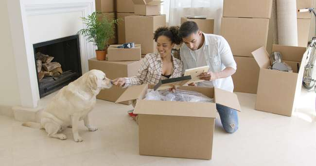Dog with owners looking at box.