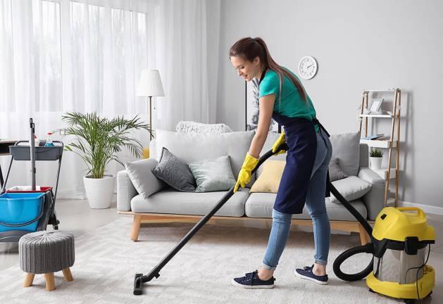 Woman vacuuming house.