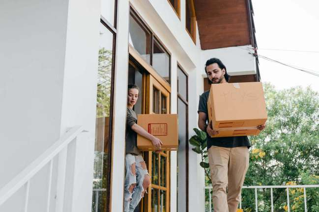 People carrying boxes out of house.
