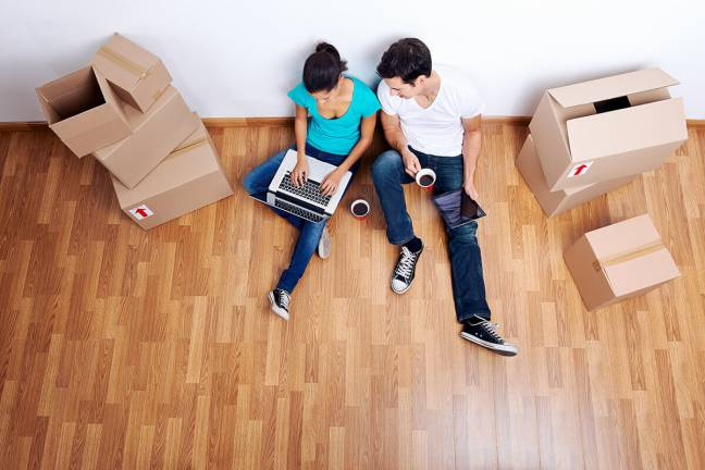 Man and woman using laptop on floor while moving.